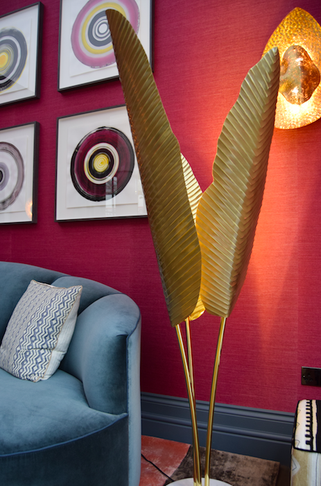 The pink wallpaper is a gorgeous backdrop for the contrasting golden details and the David Hockney painting.